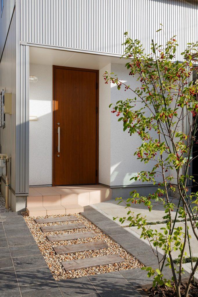 白い左官壁と木の色の玄関ドア