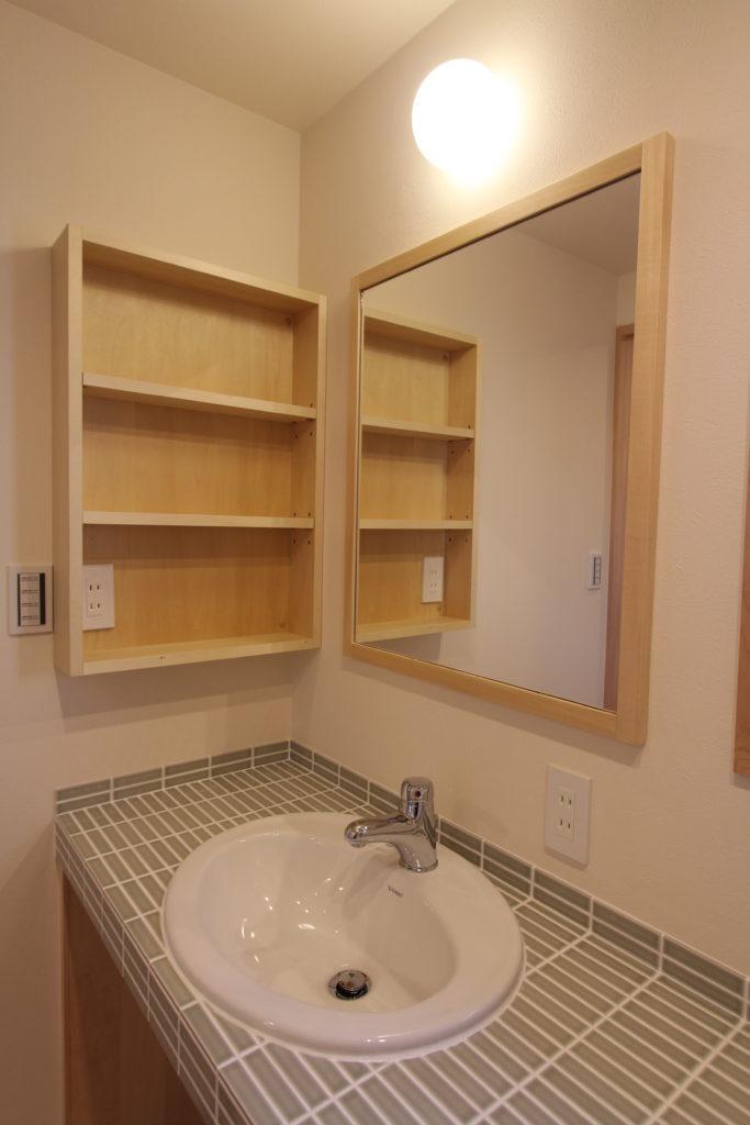 まるい洗面に木の小物棚